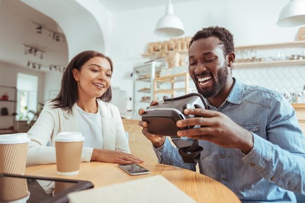 Najnowocześniejsza technologia. przyjemni młodzi przyjaciele siedzą przy stole w kawiarni i przyglądają się nowemu zestawowi vr w rękach uśmiechniętego mężczyzny