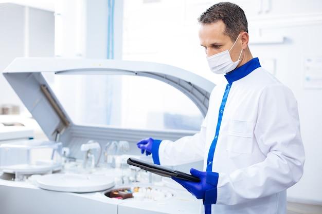 Najnowocześniejszy sprzęt. atrakcyjny, skoncentrowany naukowiec, czytający instrukcję dla innowacyjnej wirówki, trzymając tablet i stojąc w laboratorium