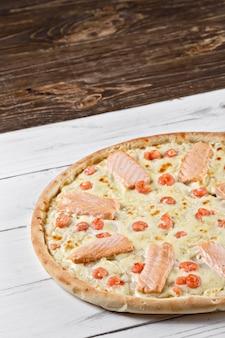 Najwyższa pizza z łososiem i krewetkami podawana na drewnianym stole. pizza z owocami morza