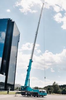 Najwyższy i największy niebieski żuraw samochodowy jest umieszczony na platformie obok dużego nowoczesnego budynku. największy dźwig samochodowy do skomplikowanych zadań.