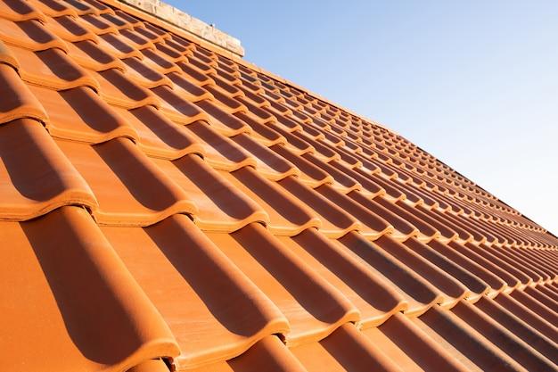 Nakładające się rzędy dachówek ceramicznych w kolorze żółtym pokrywające dach budynku mieszkalnego.