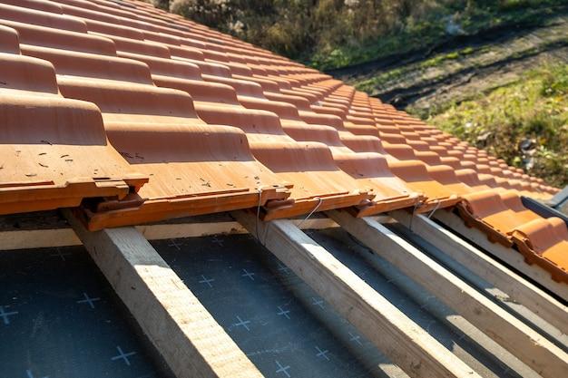 Nakładające się rzędy dachówek ceramicznych w kolorze żółtym ułożonych na deskach drewnianych pokrywających dach budynku mieszkalnego w trakcie budowy.