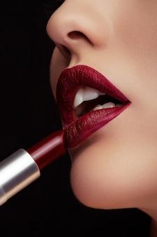 Nakładanie czerwonej szminki na usta na zdjęciu z bliska na czarnym tle. piękno i makijaż