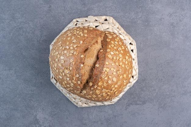 Nakładanie płatków na bochenek chleba na odwróconym koszu na marmurowym tle. zdjęcie wysokiej jakości