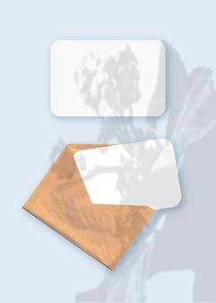 Nakładka cieni roślin na kopercie z dwoma arkuszami teksturowanego białego papieru na niebieskim tle stołu