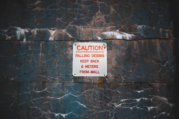 Naklejka ostrzegawcza na wyblakłej ścianie