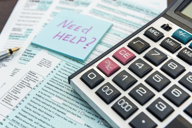 Naklejka z tekstem potrzebujesz pomocy i formularzem podatkowym 1040, długopisem i kalkulatorem. ostateczny termin. papierkowa robota
