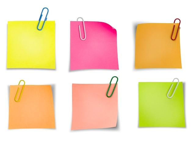 Naklejki na notatki ze spinaczami do papieru na izolowanej białej ścianie