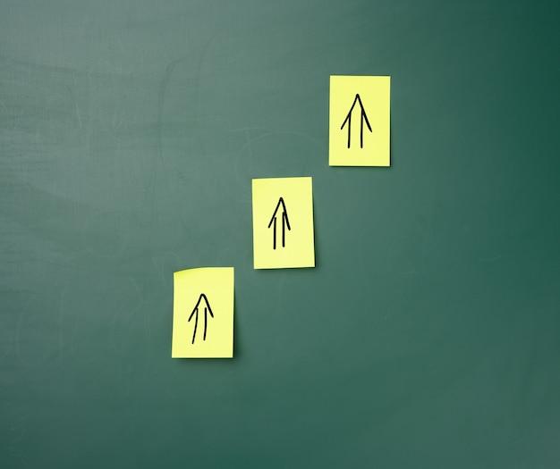 Naklejki na zielonej tablicy kredowej, narysowane strzałki w górę. koncepcja wzrostu i dynamiki