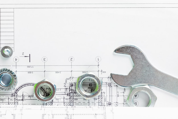 Nakrętki i śruby z bliska nad planem domu