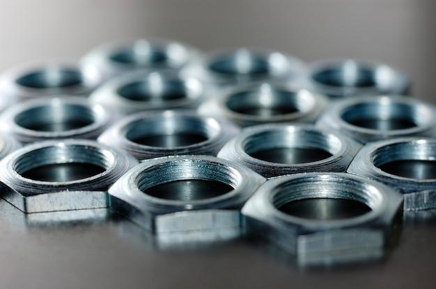 Nakrętki z chromowanego metalu z bliska w postaci plastrów miodu leżą obok siebie, tworząc obszar. koncepcja tła dla elementów złącznych i tematów budowlanych. koncepcja naprawy i części zamiennych