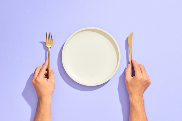 Nakrycie kolacji. biały pusty talerz i ręka trzyma złoty widelec i nóż na bzu