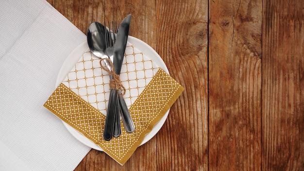 Nakrycie na obiad na tle rustykalnym. nakrycie stołu bożego narodzenia ze złotymi dekoracjami na drewnianym stole. widok z góry. skopiuj miejsce.