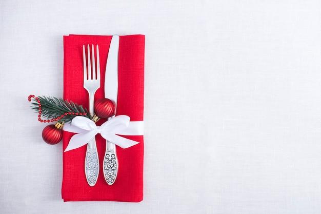 Nakrycie stołu bożego narodzenia z czerwoną serwetką na białym obrusie. widok z góry. skopiuj miejsce.