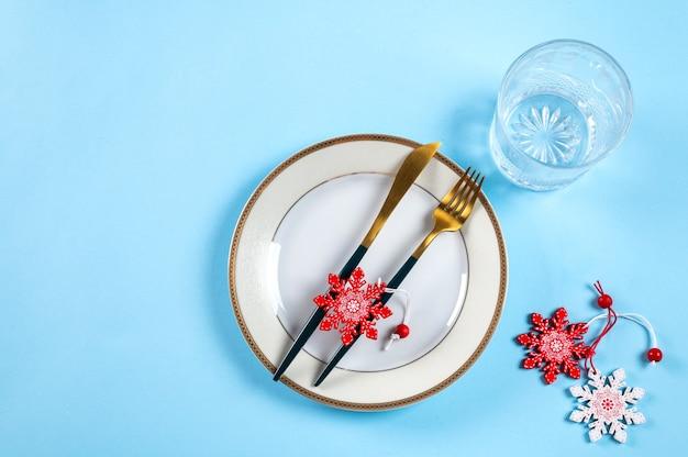 Nakrycie stołu bożego narodzenia z nowoczesnymi naczyniami i dekoracjami na niebieskim tle. widok z góry. nakrycie noworoczne. świąteczna zastawa stołowa. nakrycie na boże narodzenie. świąteczne sztućce z dekoracją.