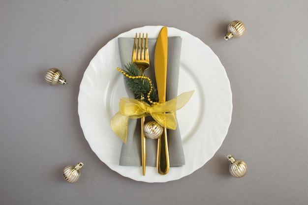 Nakrycie stołu bożego narodzenia z szara serwetka, złoty widelec i nóż na białym talerzu na szarym tle. widok z góry. skopiuj miejsce.