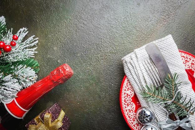 Nakrycie stołu bożonarodzeniowego z gałęzi choinki, szampanem, talerzem, nożem i widelcem na ciemnym stole, widok z góry z copyspace. święta bożego narodzenia w tle