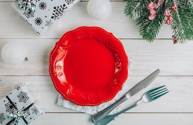 Nakrycie stołu bożonarodzeniowego z pustym talerzem, sztućcami, serwetką z dekoracjami świątecznymi