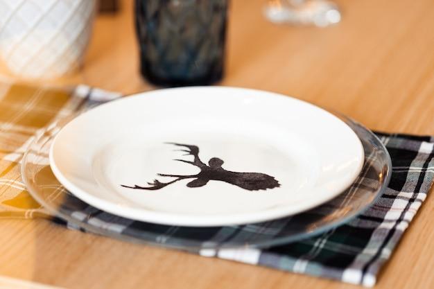 Nakrycie stołu bożonarodzeniowego z talerzem z sylwetką jelenia