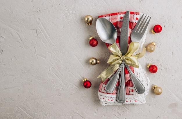 Nakrycie stołu bożonarodzeniowego ze sztućcami na serwetce i bombką ozdoby świąteczne.