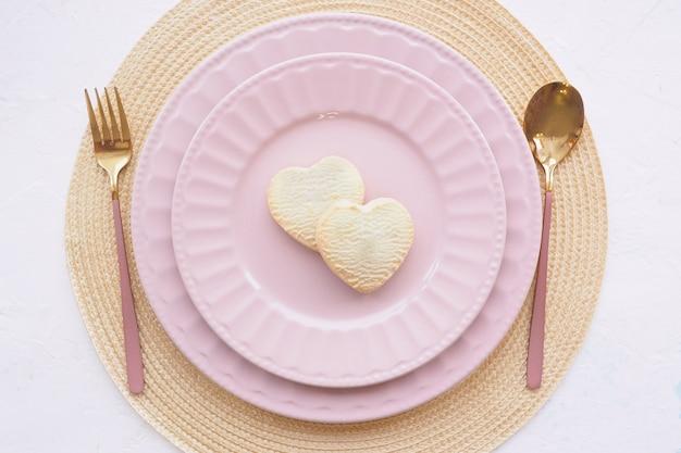 Nakrycie stołu. dwa puste różowe talerze, dwa ciasteczka w kształcie serca, łyżka i widelec na białym stole
