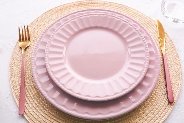 Nakrycie stołu. dwa puste różowe talerze, łyżka i widelec na białym stole