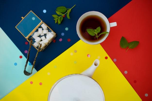 Nakrycie stołu, herbata z miętą, filiżanką i kostkami cukru w pudełku, nikt. luksusowe sztućce na obrusie, zastawa stołowa na zewnątrz