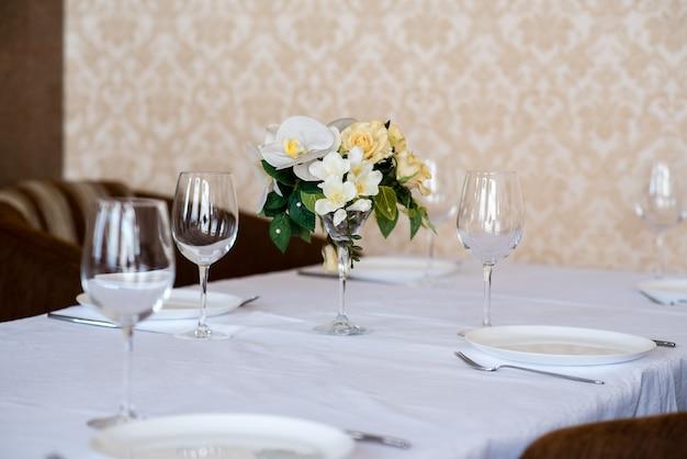 Nakrycie stołu jadalnego ozdobione kwiatami.