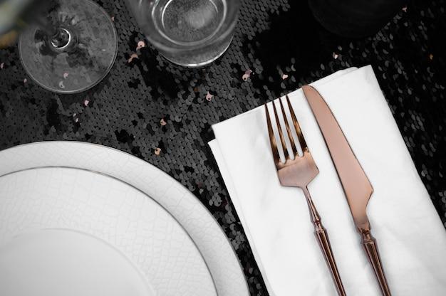Nakrycie stołu, luksusowe sztućce i zastawa stołowa na czarnym zbliżeniu, nikt. elegancka dekoracja. romantyczna uroczystość na letniej łące
