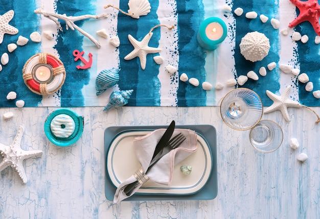 Nakrycie stołu na dzień kolumba z morskimi dekoracjami morskimi na niebieskim prążkowanym bieżniku