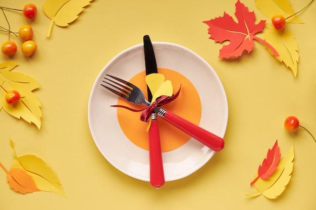 Nakrycie stołu na jesienne święto. ceramiczny talerz na żółtym papierze z papierem jesienne liście