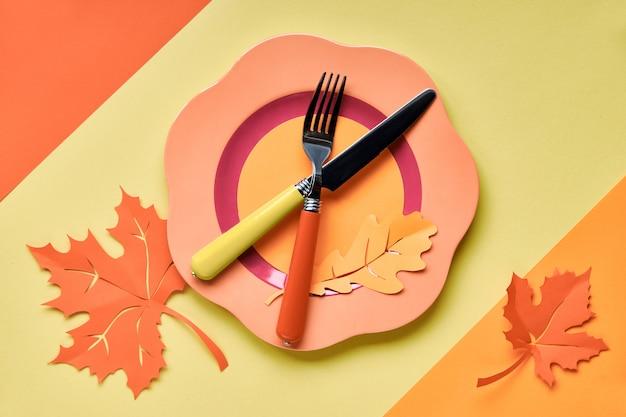 Nakrycie stołu na jesienne święto. jasny plastikowy talerz na żółtym papierze z papierem jesienne liście