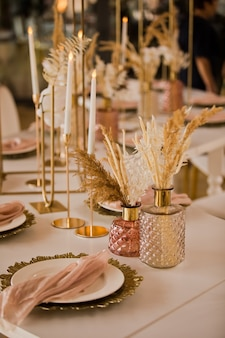 Nakrycie stołu na luksusowym weselu i piękne kwiaty na stole. dekoracje ślubne, kwiaty, dekoracje różowe i złote, świece. świąteczny wystrój stołu.