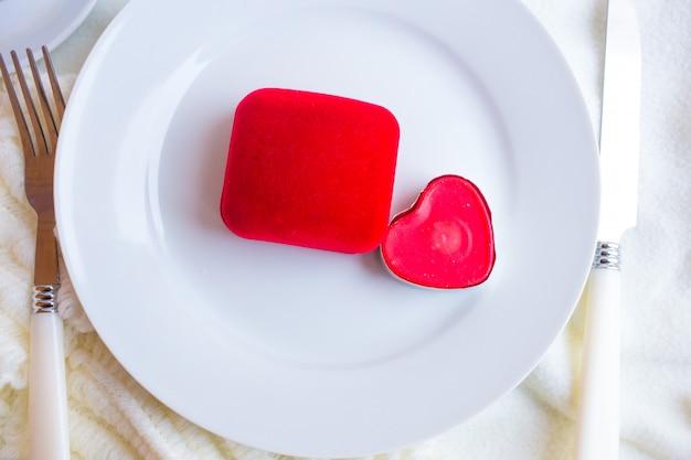 Nakrycie stołu na walentynki z czerwonym aksamitnym pudełkiem, świeczką i srebrną zastawą