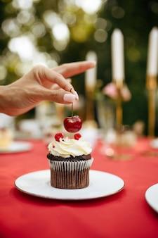 Nakrycie stołu, przyjęcie herbaciane, kobieta dekoruje ciasta świeżą wiśnią. luksusowe sztućce na czerwonym obrusie, zastawa stołowa na zewnątrz.