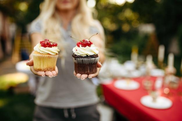 Nakrycie stołu, przyjęcie herbaciane, kobieta pokazuje świeże ciasta. luksusowe sztućce na czerwonym obrusie, zastawa stołowa na zewnątrz.