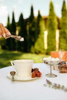 Nakrycie stołu, przyjęcie herbaciane, ręka kobiety wkłada cukier do kubka, widok z boku. luksusowe sztućce na białym obrusie, zastawa stołowa na zewnątrz.