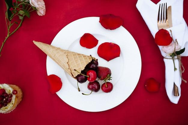 Nakrycie stołu, przyjęcie herbaciane, rożek waflowy ze świeżymi jagodami, widok z góry, nikt. luksusowe sztućce na czerwonym obrusie, zastawa stołowa na zewnątrz.