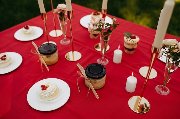 Nakrycie stołu, przyjęcie herbaciane ze słodyczami i miodem, nikt. luksusowe sztućce na czerwonym obrusie, zastawa stołowa na zewnątrz.