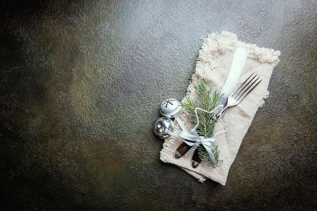 Nakrycie stołu świątecznego z gałęzi choinki, nożem i widelcem na ciemnym stole, widok z góry z copyspace. święta bożego narodzenia w tle