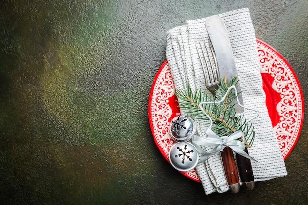 Nakrycie stołu świątecznego z gałęzi choinki, talerz, nóż i widelec na ciemnym stole, widok z góry z copyspace. święta bożego narodzenia w tle