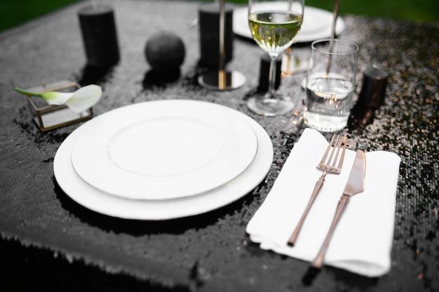 Nakrycie stołu, szklanki, świece i talerz na czarnym blacie, nikt. luksusowe sztućce, zastawa stołowa na zewnątrz, elegancka dekoracja. romantyczna uroczystość na letniej łące