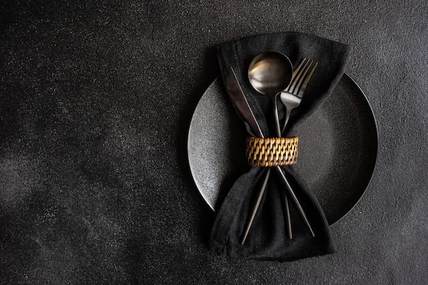Nakrycie stołu w minimalistycznym stylu z czarnymi stylowymi sztućcami na czarnym betonowym stole z miejscem na kopię