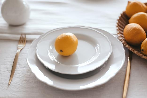 Nakrycie stołu w odcieniach bieli i żółci.