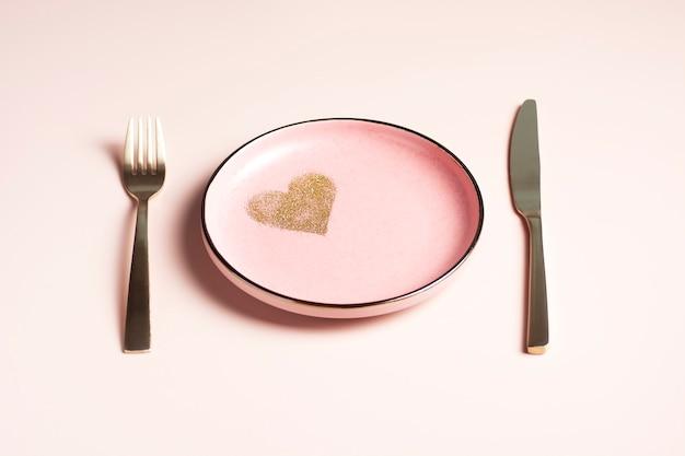 Nakrycie stołu walentynkowego, różowy talerz ze złotym sercem na pudrowym tle