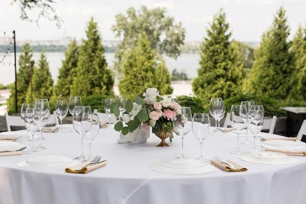 Nakrycie stołu weselnego ozdobione świeżymi kwiatami w mosiężnym wazonie. florystyka ślubna. stół bankietowy dla gości na świeżym powietrzu z widokiem na zieloną przyrodę. bukiet z róż, eustomy i liści eukaliptusa