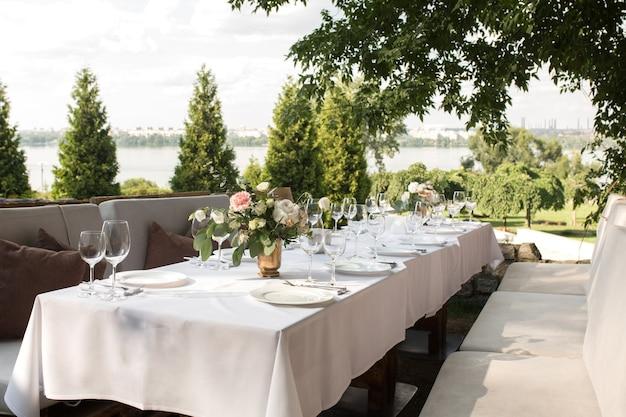 Nakrycie stołu weselnego ozdobione świeżymi kwiatami w mosiężnym wazonie