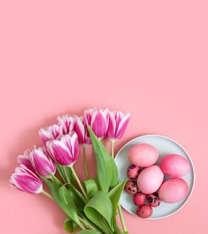 Nakrycie stołu wielkanocnego różowy z jajkami i bukietem wiosennych kwiatów tulipanów. orientacja pionowa. skopiuj miejsce, widok z góry, płaski układ.