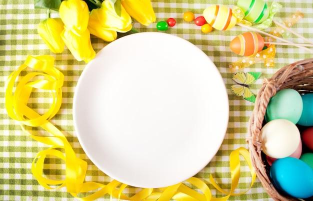 Nakrycie stołu wielkanocnego z białym talerzem, koszem kolorowych jajek, świec i żółtych tulipanów.