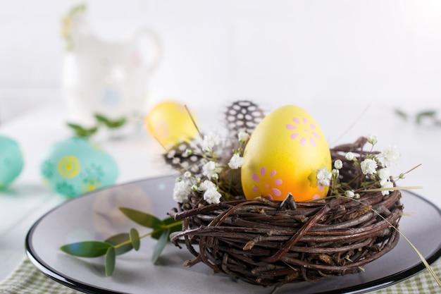 Nakrycie stołu wielkanocnego z białym talerzem, serwetką w kolorze żółtym ozdobne jajo kurze w gnieździe, kwiaty mimozy, pióra i wiosenna dekoracja wielkanocna na białym stole